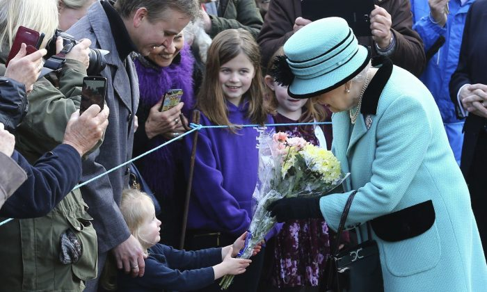 Britain's Queen Elizabeth II stops to receive flowers from 3-year old Jessica Atfield, after the queen and her husband Duke of Edinburgh, attended a church service at St Peter and St Paul church in West Newton, England on Feb. 5, 2017. (Gareth Fuller/PA via AP)