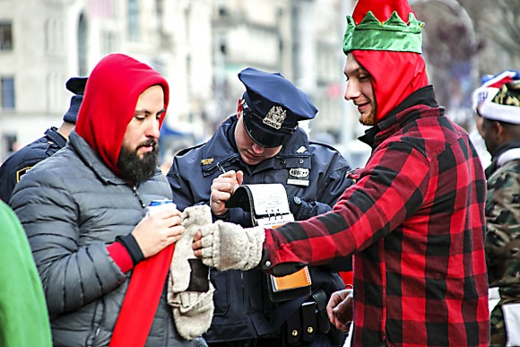 A police officer writes a ticket citing revellers for drinking alcohol in public during the annual Santacon in New York on Dec. 10, 2016. (KENA BETANCUR/AFP/Getty Images)
