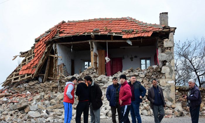 Villagers stand in front of a damaged house after two quakes, both with preliminary magnitudes of 5.3, jolted Turkey's northern Aegean coast, in Yukarikoy village Canakkale province on Feb. 6, 2017, damaging dozens of homes in at least five villages and injuring several people.(Mustafa Suicmez/DHA-Depo Photos via AP)