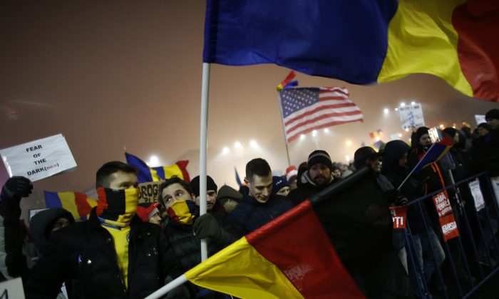 Protesters wave U.S., German and Romanian flags during a protest in Bucharest, Romania, on Feb. 6, 2017. (AP Photo/Darko Bandic)