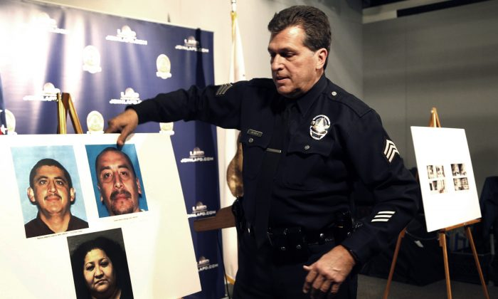 Los Angeles police Sgt. Jack Richter displays photos of arson suspects from a 1993 fire prior to a news conference in Los Angeles,] on Feb. 6, 2017. (AP Photo/Nick Ut)