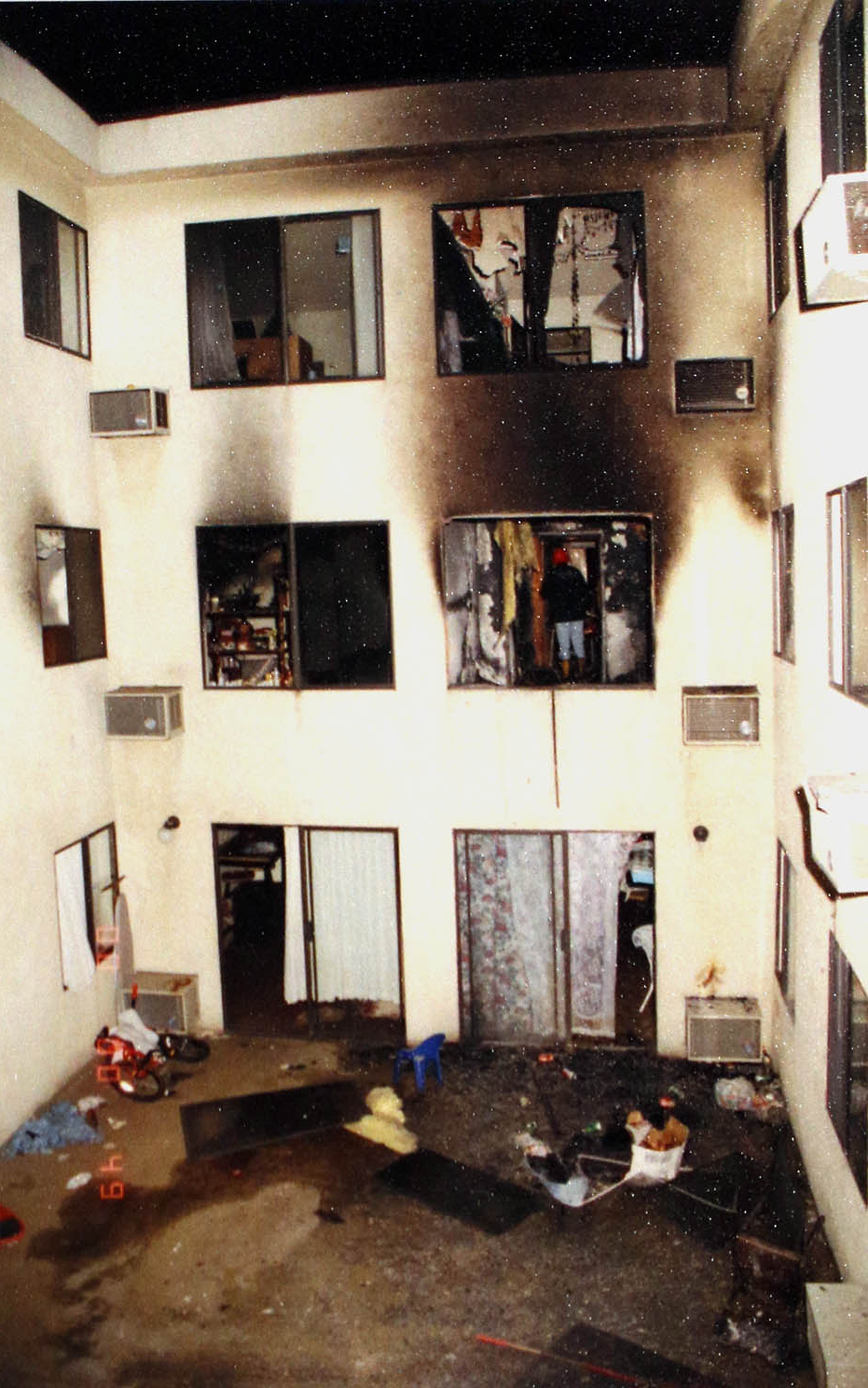 In this May 1993 photo provided by the Los Angeles Police Department, on display at a news conference, investigators attend the scene of a deadly fire that struck an apartment building in the Westlake district of Los Angeles, taking the lives of 12 people including the deaths of late-term fetuses. (Los Angeles Police Department via AP)