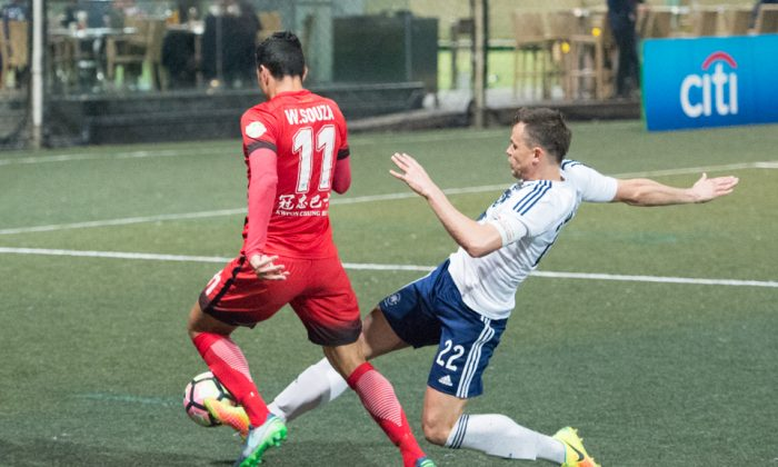 Wellingsson De Souza of Kwoon Chung Southern skips past this tackle by HKFC's Gary Czechy during their 6-0 win in the HKFA Premier league at Sports Road on Friday Feb 3.  Image Credit: (Bill Cox/Epoch Times)