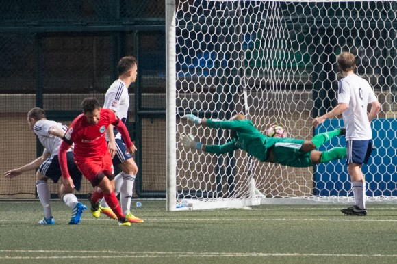 Roberto Fronza scores KC Southern's 5th goal under HKFC keeper, Issey Maholo's body as he dives to his right. (Bill Cox/Epoch Times)