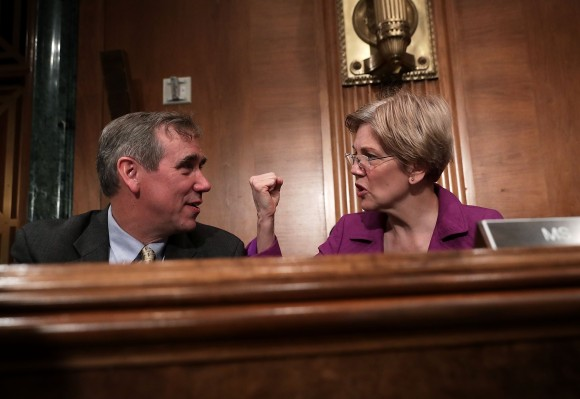 Sen. Jeff Merkley (D-OR) (L) talks to Sen. Elizabeth Warren (D-MA) (R) prior to a hearing before the Senate Banking, Housing and Urban Affairs Committee April 7, 2016 on Capitol Hill in Washington, DC. (Alex Wong/Getty Images)