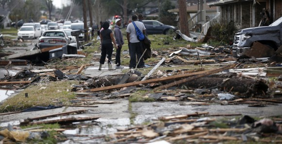 People walk amongst debris from destroyed homes after a tornado tore through the eastern neighborhood in New Orleans, Tuesday, Feb. 7, 2017. Gov. John Bel Edwards has declared a state of emergency for Louisiana after a severe storm moved across the state's southeast corner, including the parishes of Ascension, Livingston, Orleans, St. James, St. Tammany and Tangipahoa. (AP Photo/Gerald Herbert)