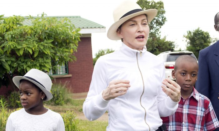 Madonna (C) tours the Mphandura orpahange near Lilongwe, Malawi with her two adopted children David Banda (R) and Mercy James on April 5, 2013. (AP Photo/Thoko Chikondi)