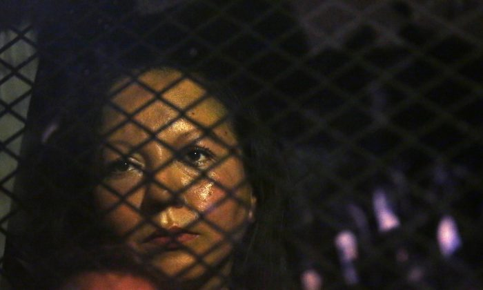 Guadalupe Garcia de Rayos is locked in a van that is stopped in the street by protesters outside the Immigration and Customs Enforcement facility in Phoenix on Feb. 8, 2017. (Rob Schumacher/The Arizona Republic via AP)