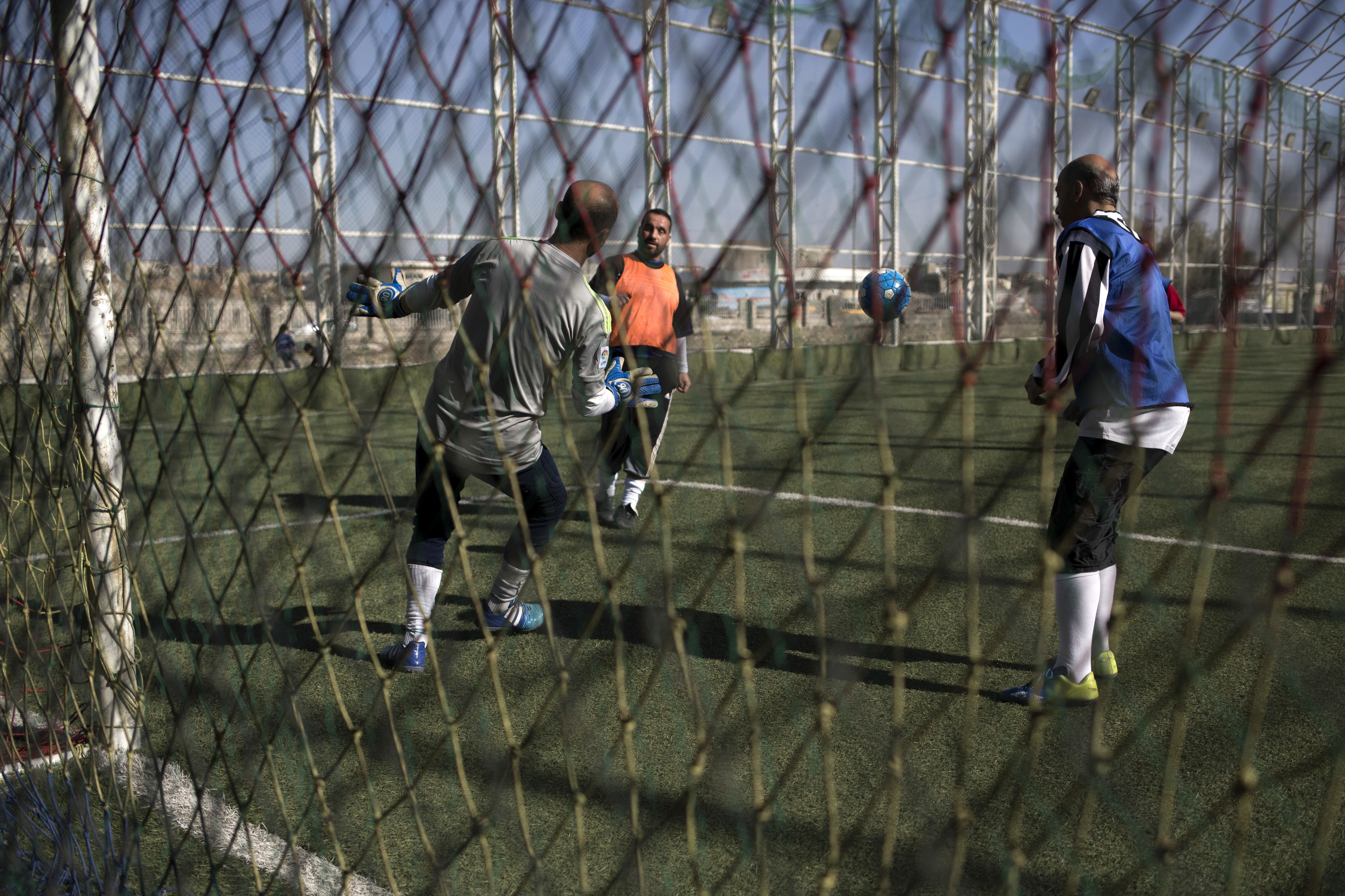 Mosul residents play soccer on a pitch in the liberated eastern part of the city on Feb. 8, 2017. (AP Photo/Bram Janssen)