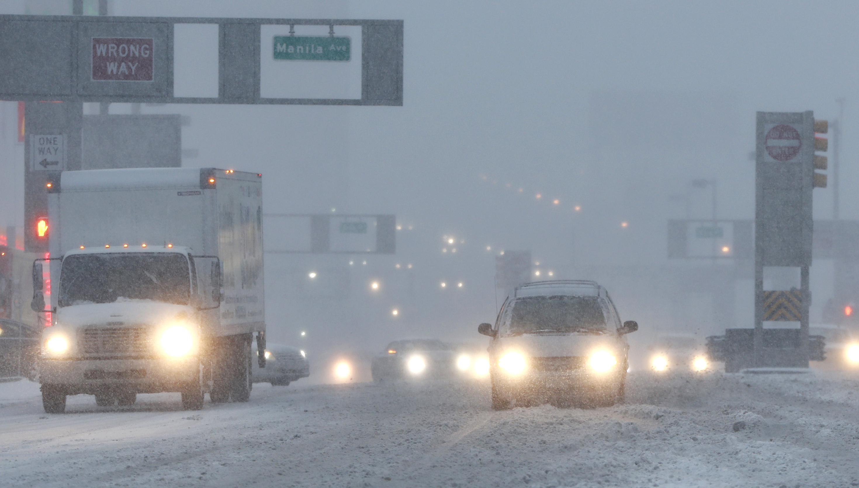 Vehicles drive drive through snow as they approach the Holland Tunnel in Jersey City, N.J., on Feb. 9, 2017. (AP Photo/Julio Cortez)