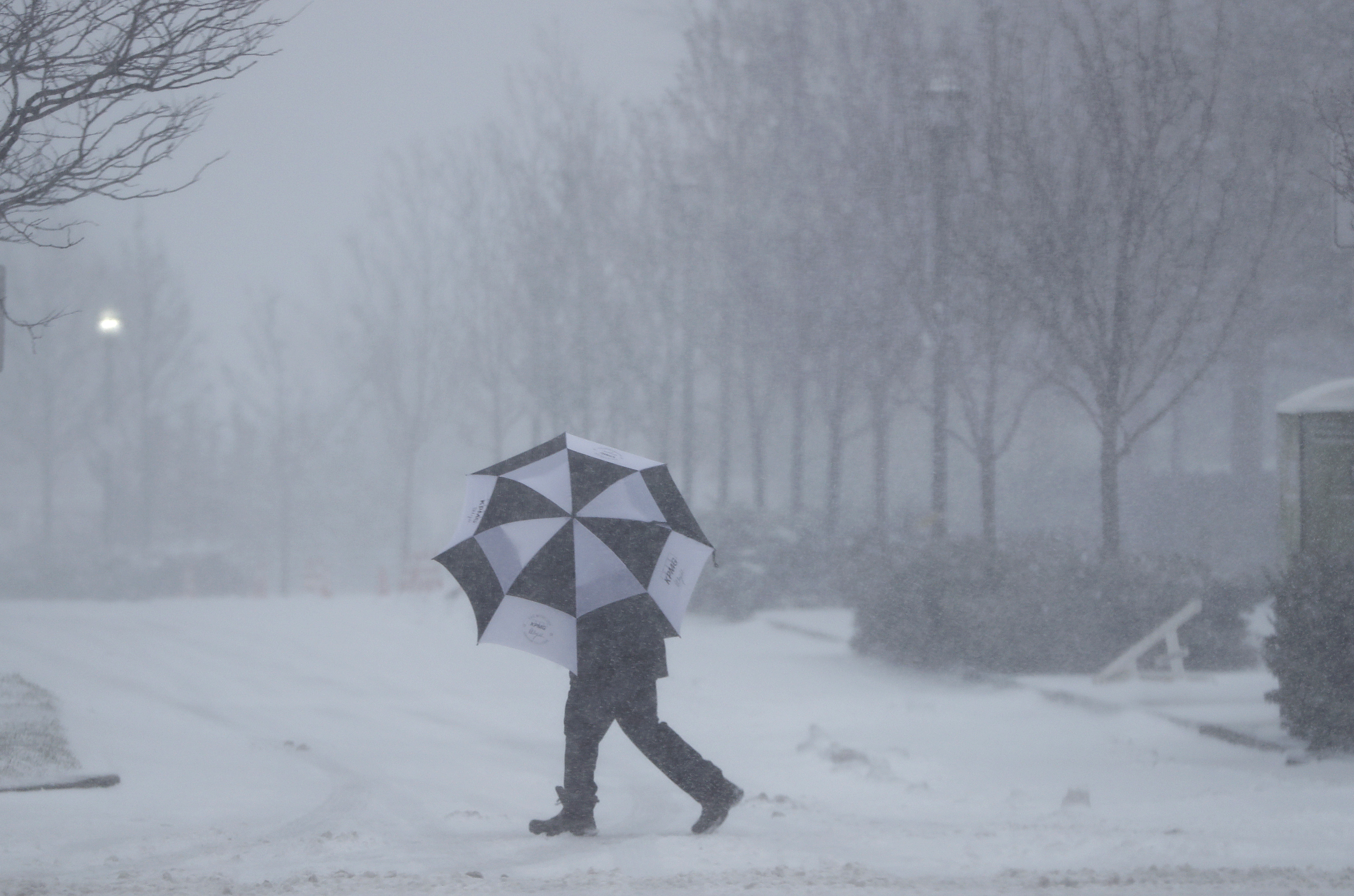 A person shields itself from falling snow with an umbrella in Jersey City, N.J., on Feb. 9, 2017.  (AP Photo/Mark Lennihan)