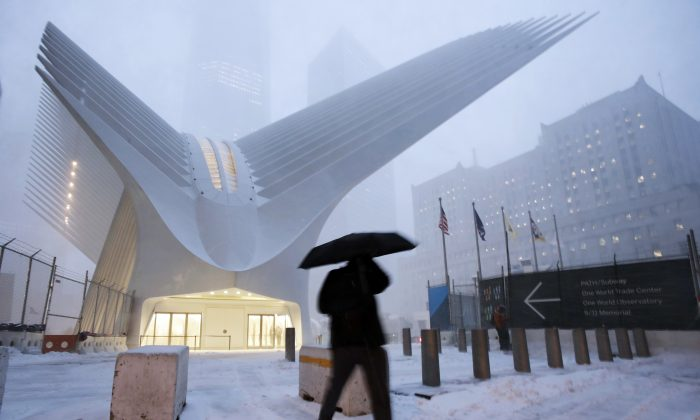 A man makes his way through wind and snow past the Oculus of the World Trade Center Transportation Hub in New York on Feb. 9, 2017. (AP Photo/Mark Lennihan)