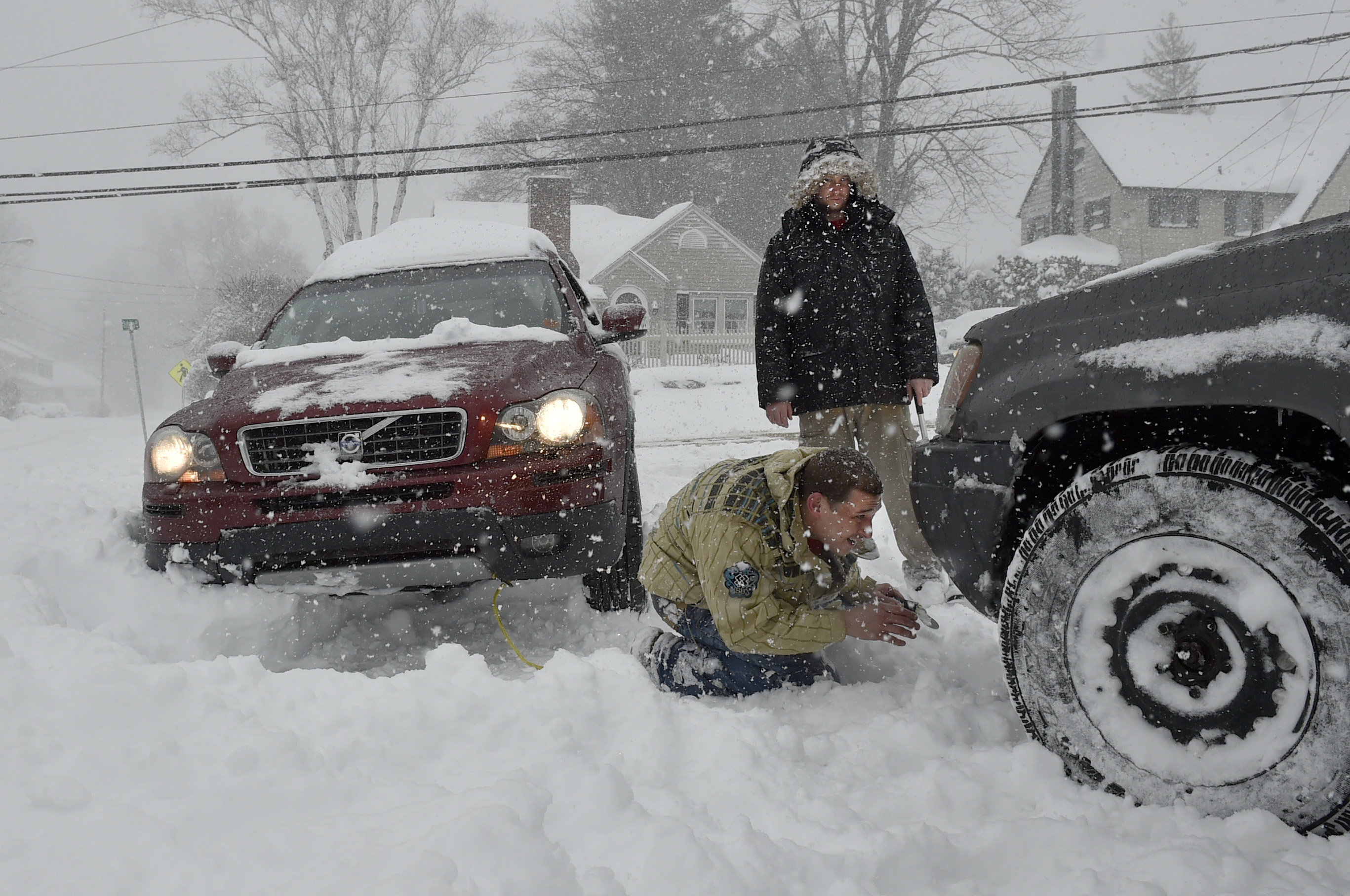 Nick Sinon looks for a place to attach his tow-strap to the front of his four wheel drive Jeep as he and Brian Brady try to help a stranded motorist get out of a snowbank in Bristol, Conn., on Feb. 9, 2017. (John Woike/Hartford Courant via AP)