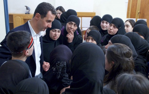 "In this photo released on Feb. 9, 2017 by the Syrian official news agency SANA, President Bashar Assad meets with former hostages released in an prisoner exchange with rebels, in Damascus, Syria. The ""First Coastal Division"" rebel faction released 55 women and children detainees on Tuesday in exchange for the government releasing 54 women prisoners of its own. (SANA via AP)"