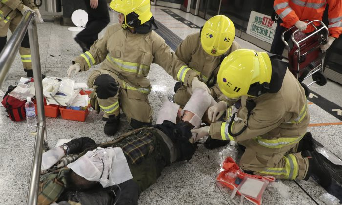 Passengers receive medical treatment from firefighters in Tsim Sha Tsui subway station in Hong Kong on Feb. 10, 2017. (Apple Daily via AP)