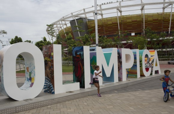 In this Feb.4, 2017 photo, children play near the Olympic Park sign in Rio de Janeiro, Brazil. Rio organizers still owe creditors about $40 million.  (AP Photo/Silvia Izquierdo)