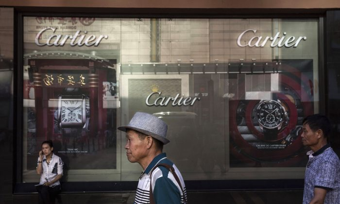 Shoppers walk pass a Cartier store in Beijing, Aug. 25, 2015. (Kevin Frayer/Getty Images)