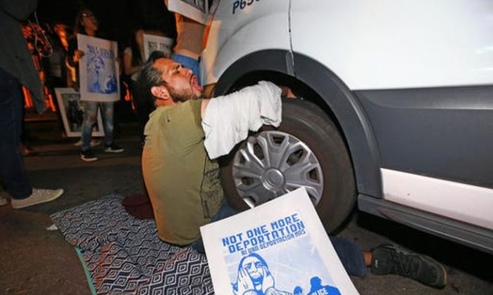 A protester locked himself to the van carrying Guadalupe Garcia de Rayos that is stopped by protesters outside the Immigration and Customs Enforcement facility, Wednesday, Feb. 8, 2017, in Phoenix. Apparently fearing her deportation, activists blocked the gates surrounding the office near central Phoenix in what the Arizona Republic says was an effort to block several vans and a bus inside from leaving. Police arrested several protesters Wednesday night after they blocked enforcement vans. (Rob Schumacher/The Arizona Republic via AP)