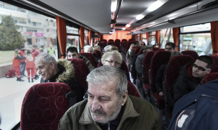 Residents of Kordelio district are seen aboard a bus after authorities ordered the evacuation of the area in order to defuse a 500-pound unexploded World War II bomb, in Thessaloniki, Greece, on Feb. 12, 2017. (AP Photo/Giannis Papanikos)