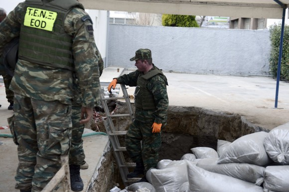 Greek Army officers conduct preparation work before they excavate an unexploded World War II bomb which was found 5 meters (over 16 feet) deep, at a gas station in Thessaloniki, Greece, on Feb. 12, 2017. (AP Photo/Giannis Papanikos)