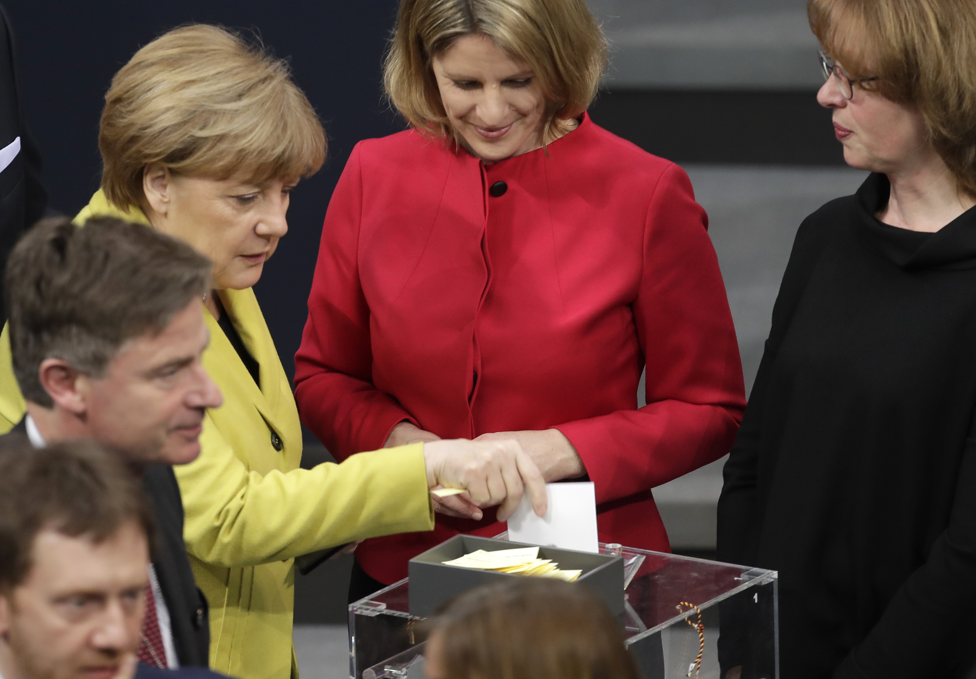 German Chancellor Angela Merkel (L) casts her ballot when a German parliamentary assembly came together to elect the country's new president in Berlin, Germany on Feb. 12, 2017. (AP Photo/Markus Schreiber)