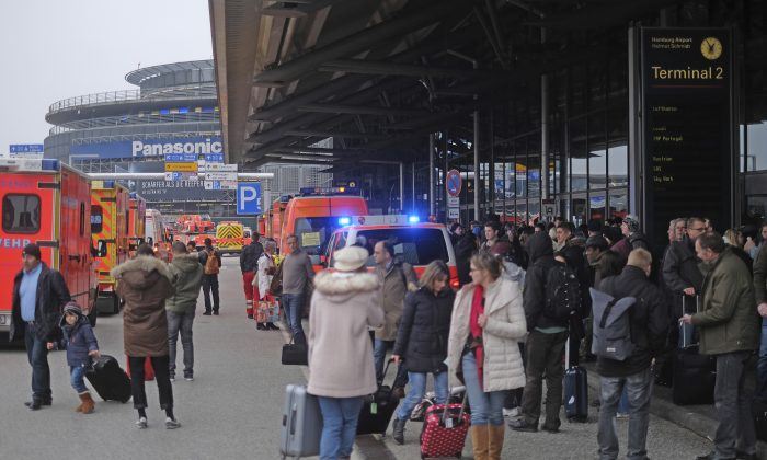 Travellers wait outside the Hamburg, northern Germany, airport on Feb. 12, 2017. (Axel Heimken/dpa via AP)