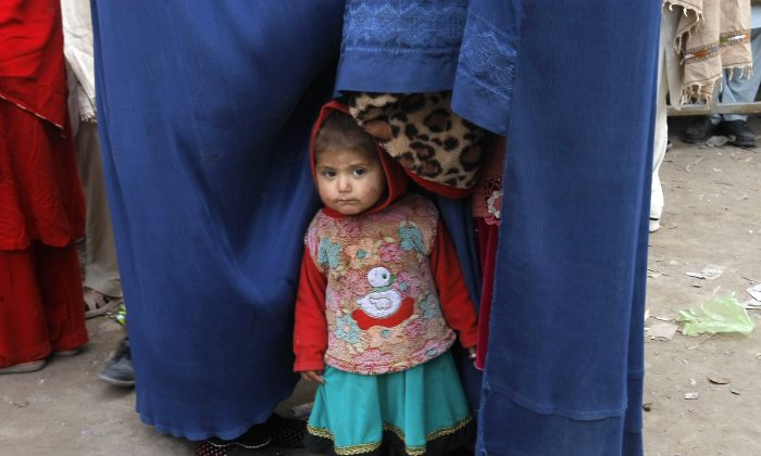 An Afghan refugee girl waits with family members for their turn to register as refugees, outside the government registration office, in Peshawar, Pakistan, on Feb. 8, 2017. (AP Photo/Mohammad Sajjad)