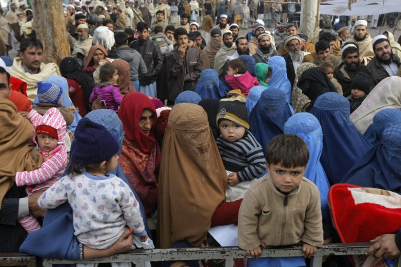 Afghan refugee families wait for their turn to be registered, outside the government registration office in Peshawar, Pakistan, on Feb. 8, 2017. (AP Photo/Mohammad Sajjad)