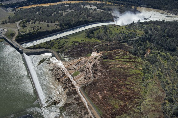 Lake water flows over the emergency spillway, bottom left, at Lake Oroville for the first time in the nearly 50-year history of the Oroville Dam in Oroville, Calif., on Feb. 11, 2017. (Randy Pench/The Sacramento Bee via AP)