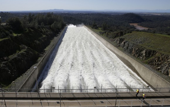 "In this Saturday, Feb. 11, 2017, photo, water flows down Oroville Dam's main spillway, in Oroville, Calif. Officials have ordered residents near the Oroville Dam in Northern California to evacuate the area Sunday, Feb. 12, saying a ""hazardous situation is developing"" after an emergency spillway severely eroded. (AP Photo/Rich Pedroncelli)"