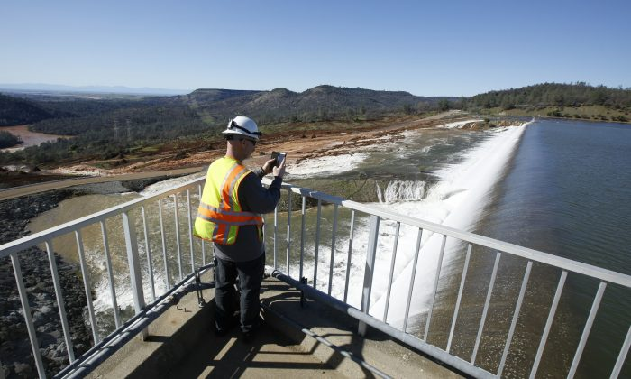 Jason Newton, of the Department of Water Resources, takes a picture of water going over the emergency spillway at Oroville Dam in Oroville, CA, on Feb. 11, 2017. (AP Photo/Rich Pedroncelli)