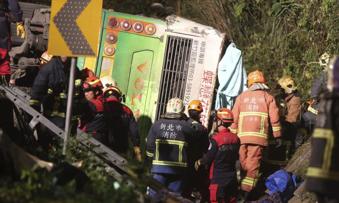 Members of rescue team at the scene where a bus collided with a car on a highway in Taipei, Taiwan on Feb. 13, 2017. (AP Photo)