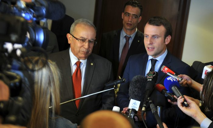 French Presidential candidate Emmanuel Macron, right, answers reporters with Algerian Foreign Minister Ramtane Lamamra in Algiers on Feb. 13, 2017. Claims made by Macron's campaign chairman Richard Ferrand Monday, assert that Russian groups are interfering with his presidential campaign but have offered little evidence to back up the claim. (AP Photo/Anis Belghoul)
