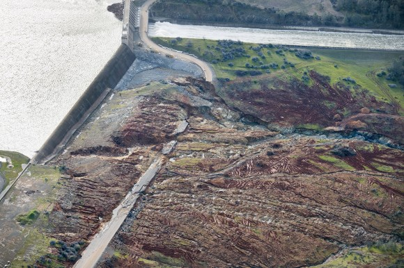 In an aerial photo, the emergency spillway at Lake Oroville shows signs of damage from the water which spilled over recently in Oroville, Calif. on Feb. 13, 2017. The water level dropped Monday behind the nation's tallest dam, reducing the risk of a catastrophic spillway collapse and easing fears that prompted the evacuation of nearly 200,000 people downstream. (Randy Pench/The Sacramento Bee via AP)