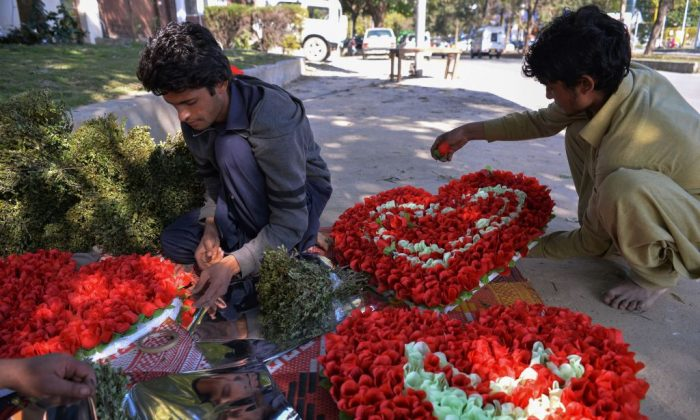 Pakistani vendors prepare heart-shaped bouquets for sale ahead of Valentine's Day along a street in Islamabad on Feb.13, 2017. (AAMIR QURESHI/AFP/Getty Images)
