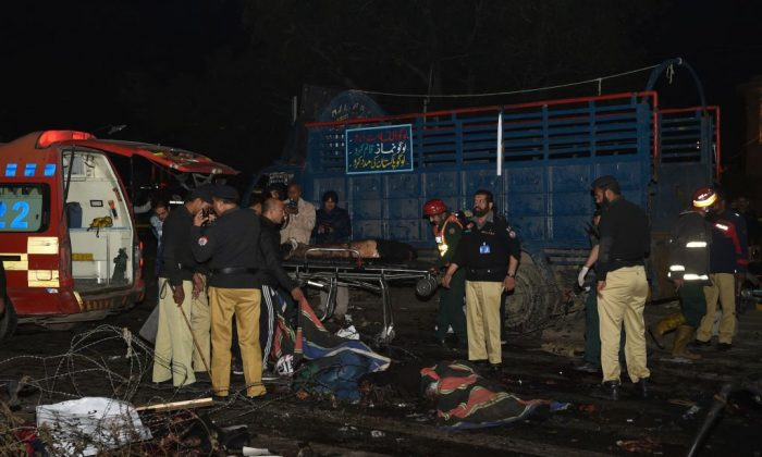 Pakistani policemen and volunteers move the bodies of victims at the site of a bomb explosion in Lahore on Feb. 13, 2017. (ARIF ALI/AFP/Getty Images)