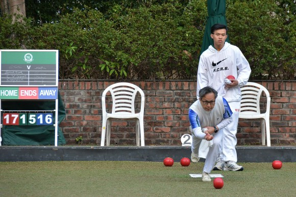 Wing Chan (delivering) of Hong Kong Football Club tried to dislodge CCC's shot in the last end of his game against youngster Simpson Cheung 18 in the HKLBA Triples League on Saturday Feb 11, 2017. Chan missed all three shots and lost the game 19-16 and CCC won with an overall result of 6:2. (Stephanie Worth)