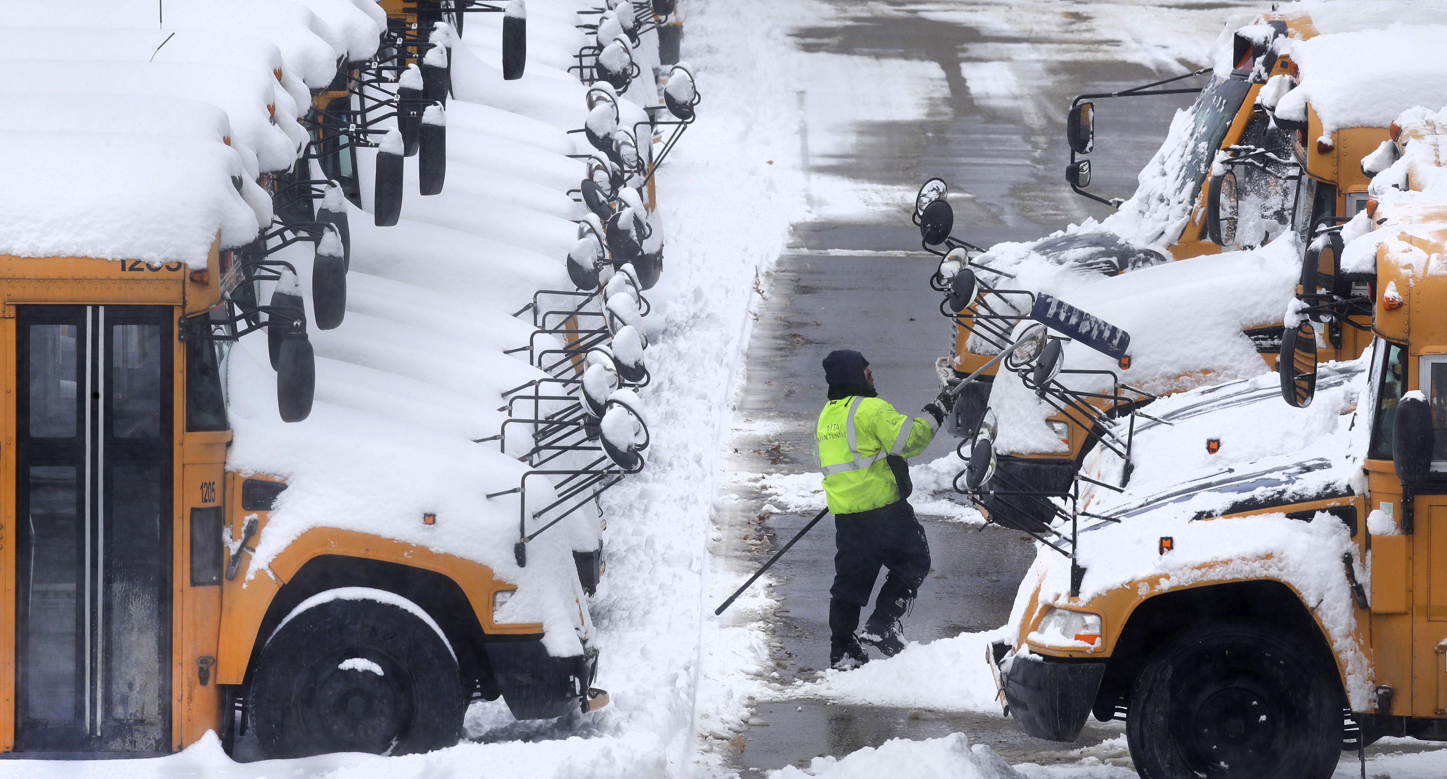 A worker clears snow off school buses, after schools were closed due to a storm, in Manchester, N.H., on Feb. 13, 2017. (AP Photo/Charles Krupa)