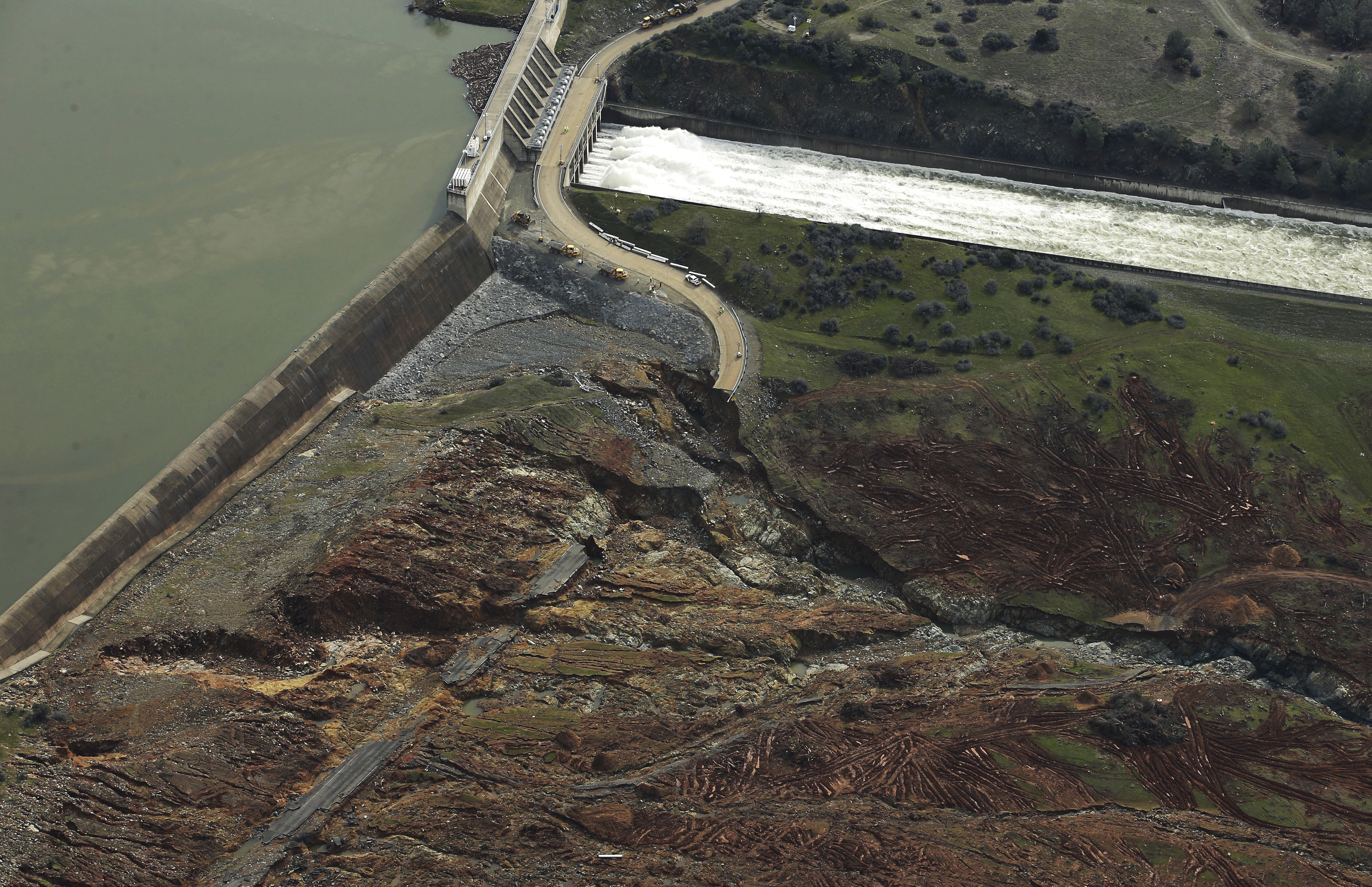 Erosion caused when overflow water cascaded down the emergency spillway is seen, bottom, as water continues to flow down the main spillway, top, of the Oroville Dam in Oroville, Calif., on Feb. 13, 2017. (AP Photo/Rich Pedroncelli)