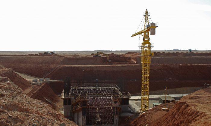 In this file photo, a crane hovers above the site of a new shaft under construction at the Oyu Tolgoi mine site in Khanbogd village, Umnugobi province, Mongolia, on Nov. 7, 2009. (AP Photo/Ganbat Namjilsangarav, File)
