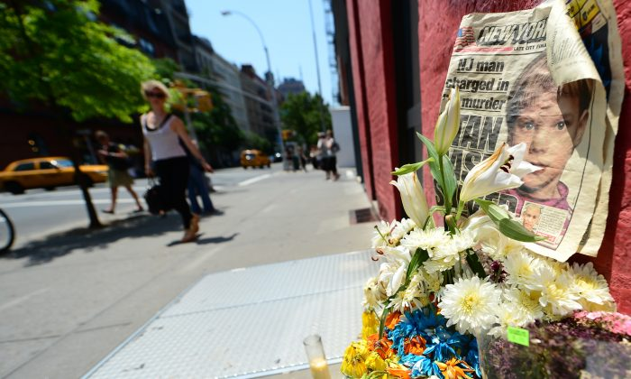 People walk past a street shrine to six-year-old Etan Patz, who disappeared 33 years ago, set in front of the building where suspect Pedro Hernandez confessed to have strangled the boy in New York on May 29, 2012. (EMMANUEL DUNAND/AFP/GettyImages)