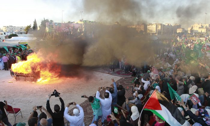 Jordanian supporters of the Muslim Brotherhood set fire to a mock Israeli tank during a protest to celebrate the 'Gaza victory' in the war against Israel, in the capital Amman on Aug. 8, 2014. (KHALIL MAZRAAWI/AFP/Getty Images)