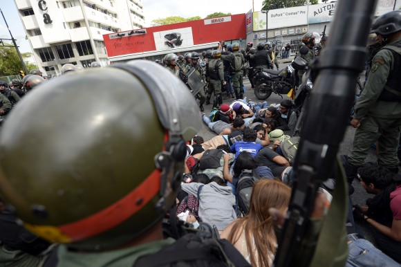 National Guard personnel in riot gear arrest students during an anti-government demonstrators in Caracas on May 14, 2014. About 80 demonstrators were arrested during a protest as they request the immediate release of youth detained in recent days. (JUAN BARRETO/AFP/Getty Images)
