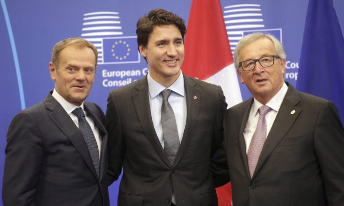 (L-R) European Council President Donald Tusk, Prime Minister Justin Trudeau, and European Commission President Jean-Claude Juncker, greet each other as they arrive for an EU-Canada summit to sign the Comprehensive Economic and Trade Agreement in Brussels on Oct. 30, 2016. The European Parliament has approved the deal, but it still has to be ratified by Canada and various European parliaments. (AP Photo/Olivier Matthys)