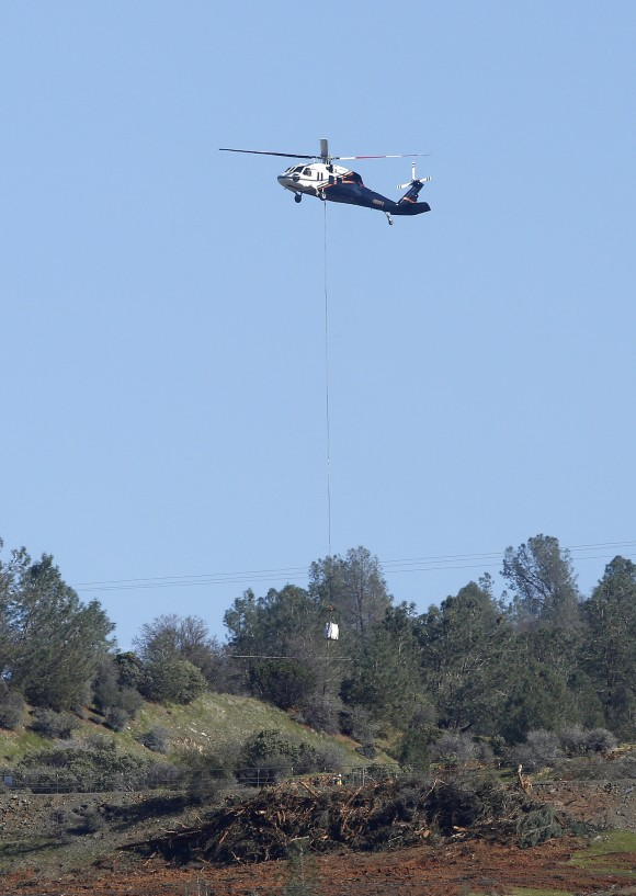 A helicopter lowers a load of rocks to fill in a hole near the Oroville Dam's emergency spillway, Tuesday, Feb. 14, 2017, in Oroville, Calif. The barrier, at the nation's tallest dam, is being repaired after authorities ordered mass evacuations for everyone living below the lake out of concerns the spillway could fail and send a 30-foot wall of water roaring downstream. (AP Photo/Rich Pedroncelli)