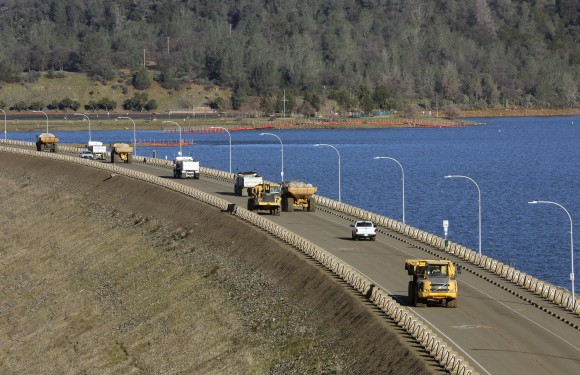 Truck after truck line the Oroville Dam roadway as the effort to stabilize the emergency spillway continues Tuesday, Feb. 14, 2017, in Oroville, Calif. Officials say the decision to lift the evacuation order for nearly 200,000 people living below a damaged dam in California has taken into account updated weather forecasts. A storm later this week is expected to be colder, with less rain. (Michael Macor/San Francisco Chronicle via AP)