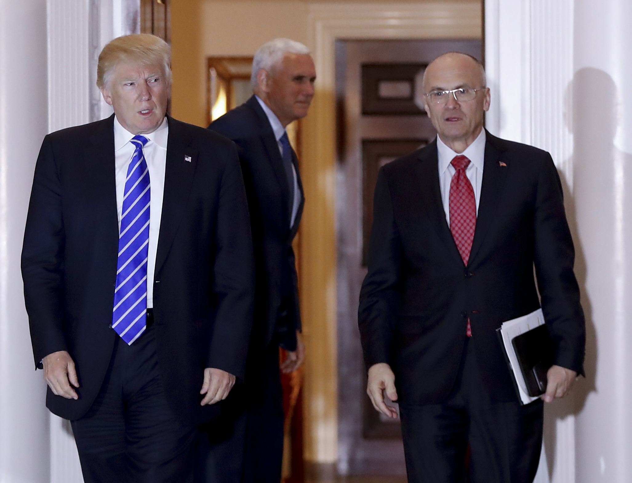 Then-President-elect Donald Trump walks Labor Secretary-designate Andy Puzder from Trump National Golf Club Bedminster clubhouse in Bedminster, N.J., on Nov. 19, 2016. (AP Photo/Carolyn Kaster, File)