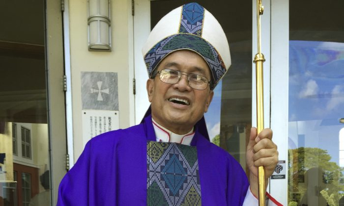 Archbishop Anthony Apuron stands in front of the Dulce Nombre de Maria Cathedral Basilica in Hagatna, Guam in this November 2014 file photo. The Pacific Daily News reports that Cardinal Raymond Burke is scheduled to interview a former altar boy who says he was sexually abused by Guam Archbishop Anthony Apuron. (AP Photo/Grace Garces Bordallo, File)