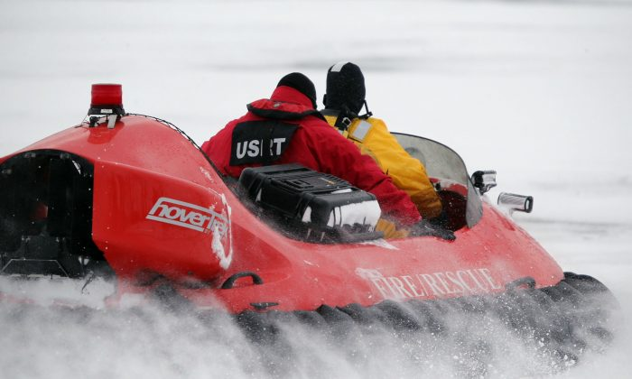 In this Feb. 13, 2017 photo, rescue crews use a hovercraft to search the frigid waters of Conesus Lake in Livonia, N.Y., for two missing snowmobilers who are believed to have fallen through the ice. Not-so-frozen lakes have claimed several snowmobilers across the Northeast so far in a relatively mild winter. (Max Schulte/Democrat & Chronicle via AP)