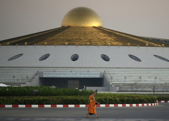 A Buddhist monk walks inside Wat Dhammakaya temple in Pathum Thani province, Thailand, on Feb. 16, 2017. (AP Photo/Sakchai Lalit)